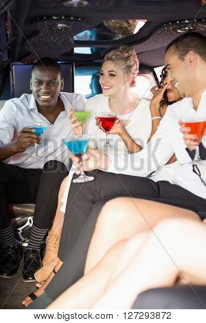 Well dressed people drinking cocktails in a limousine on a night out