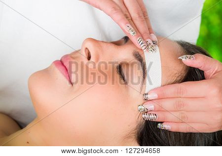 Closeup womans face receiving facial hair wax treatment, beauty and fashion concept.