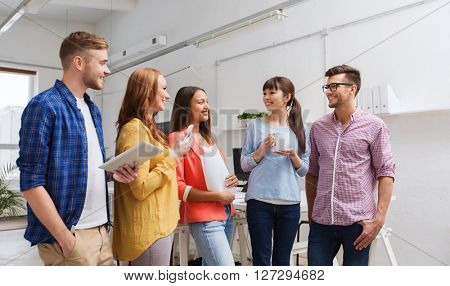 business, communication, startup and people concept - happy international creative team or students on coffee break talking at office