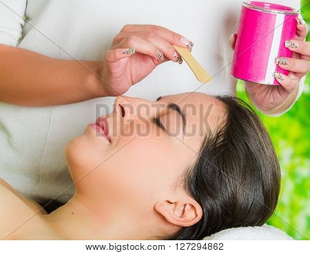 Closeup womans face receiving facial hair waxing treatment, hand using wooden stick to apply wax, beauty and fashion concept.