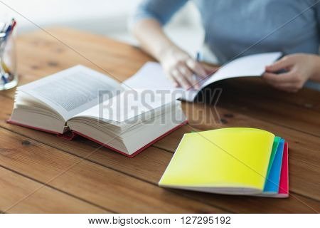 high school, education, people and learning concept - close up of young student or woman with book and notebooks at home