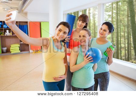 pregnancy, sport, fitness, people and healthy lifestyle concept - group of happy pregnant women with sports stuff taking selfie by smartphone in gym over natural window view background