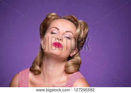 Close-up portrait of beautiful blond pin-up girl with her eyes closed isolated on violet. Tired blond lady with red lips posing in photo studio.