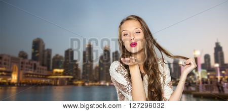 people, travel, tourism, holidays and fashion concept - happy young woman or teen girl in fancy dress with sequins and long wavy hair sending blow kiss over evening city waterfront background