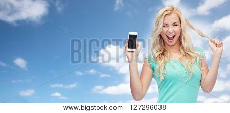 emotions, expressions, technology and people concept - smiling young woman or teenage girl showing blank smartphone screen and winking over blue sky and clouds background