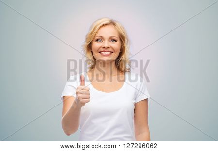 gesture, advertisement and people concept - smiling woman in blank white t-shirt showing thumbs up over gray background