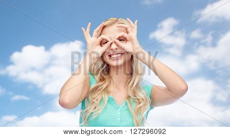 fun, emotions, expressions and people concept - smiling young woman or teenage girl looking through glasses made of fingers over blue sky and clouds background