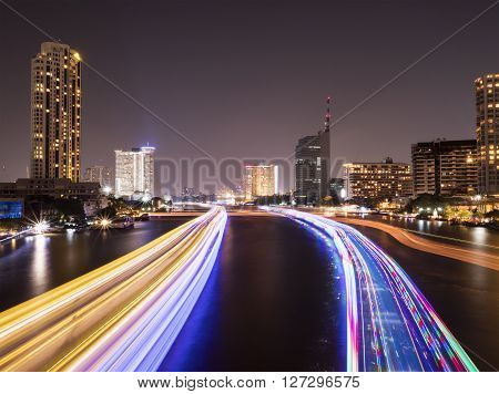 The light trails from boat on the river and modern building Night light at Chao Phraya River in Bangkok Thailand