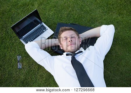 Young handsome freelance man lying on the leather bag in the park near his laptop. Man resting after his hard working day with his hands on the nape.