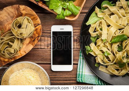 Cooked tagliatelle pasta ingredients and a smartphone