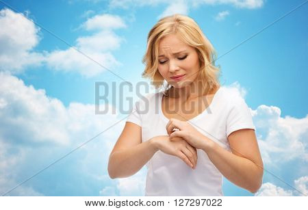 people, healthcare, dermatology, allergy and health problem concept - unhappy woman suffering from hand inch over blue sky and clouds background