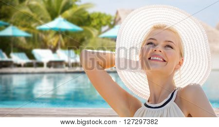 people, summer holidays, travel, tourism and vacation concept - beautiful woman in sun hat enjoying summer outdoors over exotic hotel resort beach with swimming pool and sunbeds background