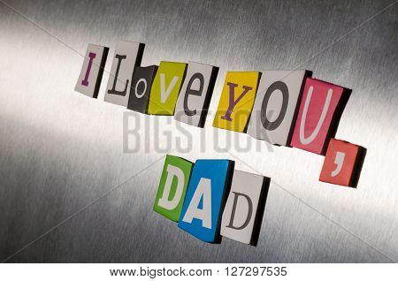 Text love you Dad for father's day  with color magazine letter clippings on short vintage metal surface.