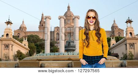 people, travel, tourism and fashion concept - happy young woman or teen girl in casual clothes and sunglasses over national museum of barcelona background