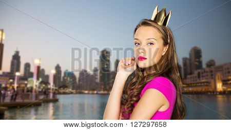 people, holidays and fashion concept - young woman or teen girl in pink dress and princess crown over evening city waterfront background