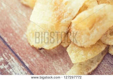 fast food, junk-food, cuisine and eating concept - close up of crunchy potato crisps on wooden table