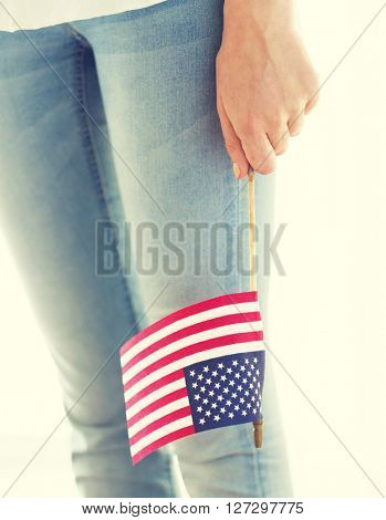 independence day, celebration, patriotism and holidays concept - close up of woman legs and hand holding american flag at 4th july party