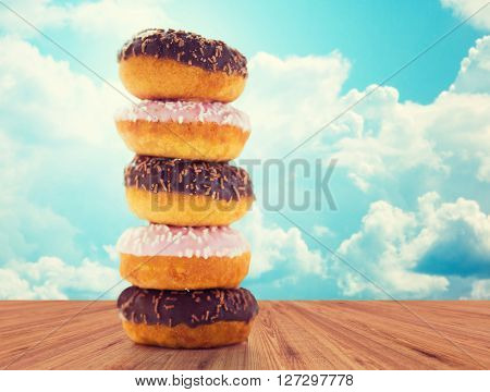 food, junk-food and eating concept - close up of glazed donuts pile on wooden table over blue sky and clouds background