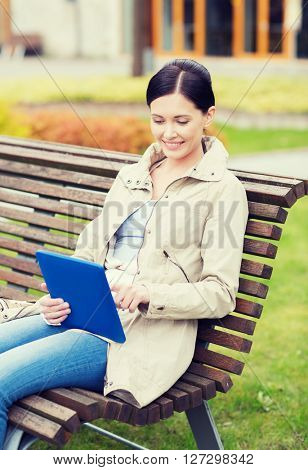 leisure, technology, communication and people concept - smiling woman with tablet pc computer sitting on bench in park
