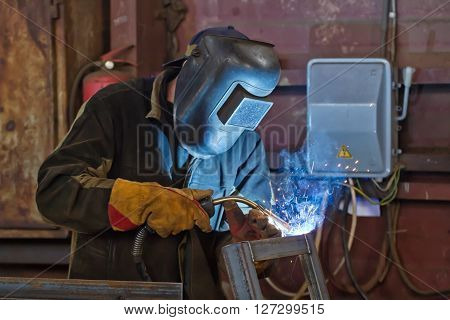 welder fabricates steel structures using semi-automatic welding in shielding gases