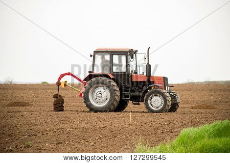 tractor digging holes for tree planting - copy space