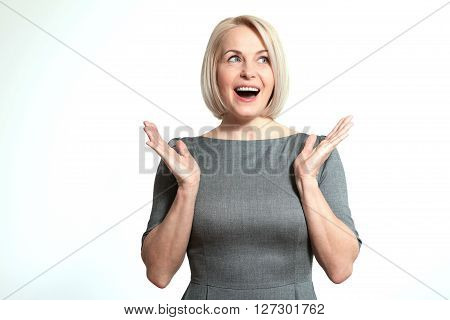 Surprised happy woman looking sideways in excitement. Isolated over white background. Portrait of happy aged woman.