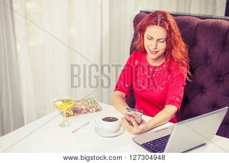 outdoor portrait of a young girl she works as a freelancer in a cafe drinking a delicious hot Cup of coffee from text send mail loads the photo instagram freelancer drinking cappuccino