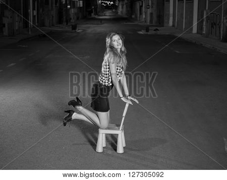 pretty blonde woman kneeling in child seat in the street at night