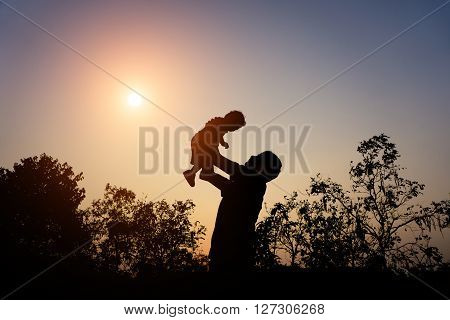 Silhouette Of Father With Her Toddler Against The Sunset