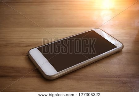 Smart Phone With Blank Screen Lying On Wooden Table