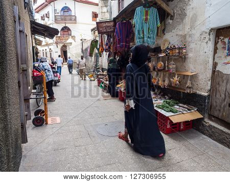 STONE TOWN ZANZIBAR - MARCH 29 2016: Local people walking on one of the streets in Stone Town the capital of Zanzibar. Stone Town is famous for its colonial architecture.