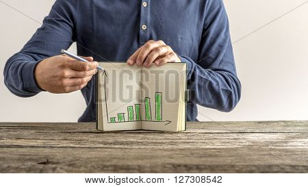 Businessman showing his notebook with financial graphs representing annual growth and progress of the company.