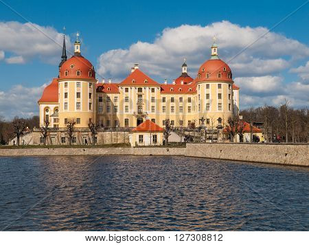 Baroque castle of Moritzburg with yellow facade and red roof on sunny day, Saxony, Germany