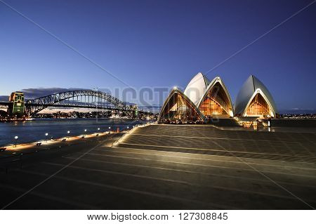 SYDNEY AUSTRALIA - OCTOBER 10 2010: Night view of the Sydney Opera House and Harbor Bridge from behind the fence of the Tarpeian Way (Sydney Australia)