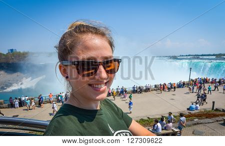 Young smiling woman with sunglasses on beautiful sunny springtime morning at Niagara Falls.  People & tourists in background see, hear, and feel the power of the Falls.