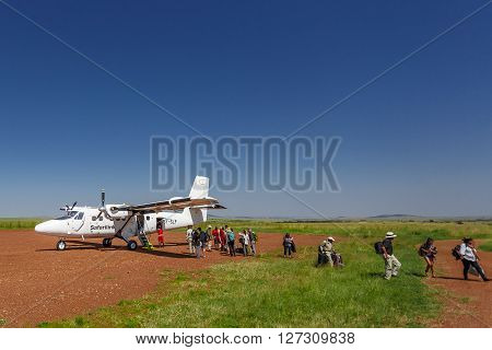 MAASAI MARA KENYA - JUNE 24 2015: Safalink plane has landed at the Maasai Mara field airport (Kenya) and its passengers are leaving the aircraft