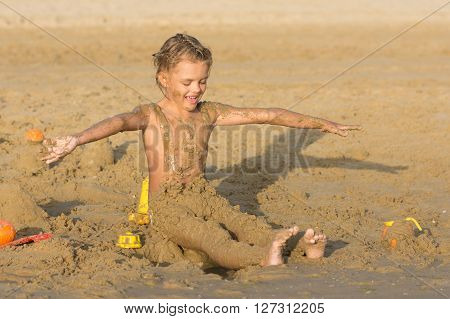 Satisfied six year old girl to roll yourself wet sand on the beach
