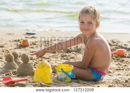 Pleased With The Child On A Sandy Beach At The Water Points At Cakes Hired By Sand