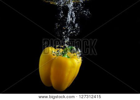 Fresh paprika splash in water with air bubbles. Yellow paprika in water on black background. Healthy food. Wash vegetables.