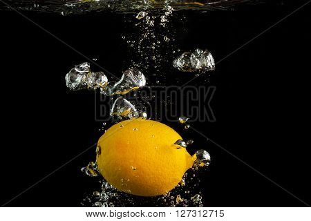 Fresh lemon falling into the water with a splash and air bubbles. Yellow lemon in water on black background. Healthy food. Wash fruits.