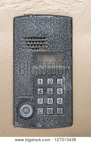 Electronic access control door box with numeric keypad closeup, weathered metal. Password code security keypad system protection in public building. Security intercom number keypad at apartment door.