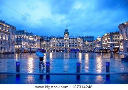 Trieste, Italy, 30 May 2013: a pedestrian with umbrella cross Piazza Unita Italia of Trieste at night  after the rain