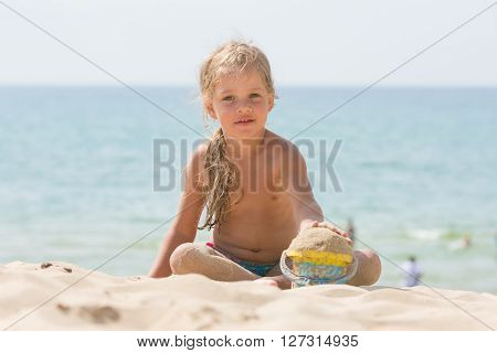 Baby Girl Playing With Sand And Vederochkom Child On The Sea Beach