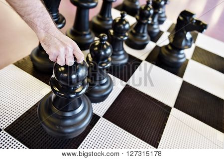 Hand moving the black pawn on a giant chess game