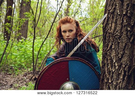 Redhead scandinavian young woman with sword and shield posing in a wood