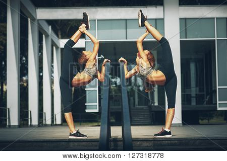 Two twins sisters stretching outdoor during the day