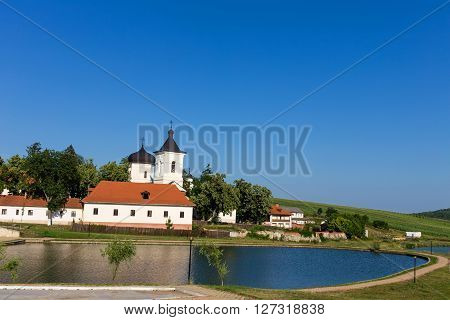 Moldovan orthodoxal monastery near the lake. Picturesque scenery at summer day with bright blue sky.