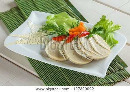 Stuffed pike fish - sliced on white plate with parshley salad carrot