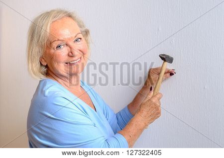 Smiling capable elderly woman doing DIY standing holding a nail and hammer as she prepares to knock it into a wall upper body isolated on white