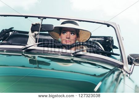 Vintage 1960 Fashion Woman With Hat Looking In Mirror Of Convertible Car.